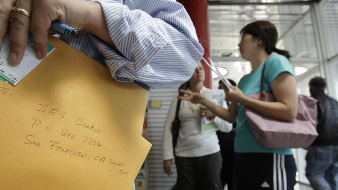 A man waits in a long line at U.S. Post Office in San Jose, Calif., to turn in his federal and state tax forms, Monday, April 18, 2011. (AP Photo/Paul Sakuma)