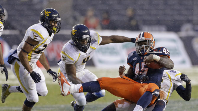West Virginia linebacker Josh Francis (4) watches as cornerback Pat Miller, right rear, brings down Syracuse running back Jerome Smith (45) during the first half of the Pinstripe Bowl NCAA college football game at Yankee Stadium in New York, Saturday, Dec. 29, 2012. (AP Photo/Kathy Willens)
