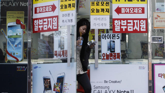 Banners advertising Samsung Electronics' Galaxy Note II and Apple's iPhone 5 are displayed on a door at a mobile phone shop in Seoul, South Korea Friday, Jan. 25, 2013. Samsung Electronics Co. said quarterly profit soared 76 percent, boosted by the popularity of its Galaxy smartphones, which outsold the iPhone for a fourth straight quarter. But the company said Friday it expects earnings to decline during the current quarter because of seasonally low demand for consumer electronics. (AP Photo/Ahn Young-joon)