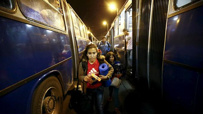 Migrants walk to a bus, which is supposed to leave for Austria and Germany, next to Keleti train station in Budapest, Hungary