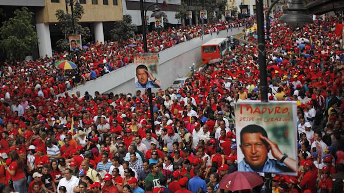 "Supporters of Venezuela's acting President Nicolas Maduro gather outside the national electoral council as he registers his candidacy for president to replace late President Hugo Chavez in Caracas, Venezuela, Monday, March 11, 2013. The poster of Chavez reads in Spanish ""Maduro, from my heart."" Presidential elections were announced to take place on April 14, after Maduro announced on March 5 that Chavez had died. (AP Photo/Rodrigo Abd)"