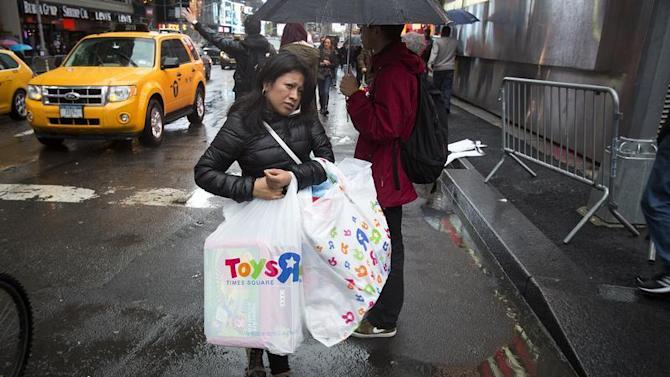 A woman carries bags of purchases though Times Square in New York