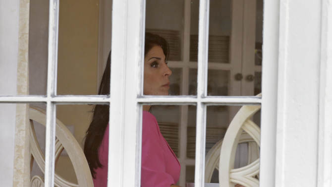 Jill Kelley sits inside her home Tuesday, Nov 12, 2012 in Tampa, Fla. Kelley is identified as the woman who allegedly received harassing emails from Gen. David Petraeus' paramour, Paula Broadwell. She serves as an unpaid social liaison to MacDill Air Force Base in Tampa, where the military's Central Command and Special Operations Command are located. (AP Photo/Chris O'Meara)