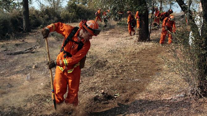 An inmate cleans out brush to build a fire line for structure protection from the Ponderosa Fire near Paynes Creek, Calif., Wednesday, Aug. 22, 2012. The Ponderosa Fire, which has scorched about 38 square miles since Saturday, was 50 percent contained Wednesday morning, according to the California Department of Forestry and Fire Protection. The threat to homes about 35 miles east of Redding has dropped from 3,500 earlier this week to roughly 200 residences. (AP Photo/Rich Pedroncelli)