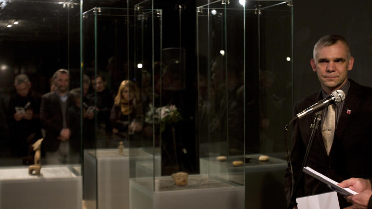 German police officer Eckhard Laufer, right, addresses visitors to the exhibition for returned artifacts from Germany to the Kosovo Archeology Museum in capital Pristina on Friday, Feb. 22, 2013. The artifacts are believed to have been stolen during the 1998-99 Kosovo war. (AP Photo / Visar Kryeziu)
