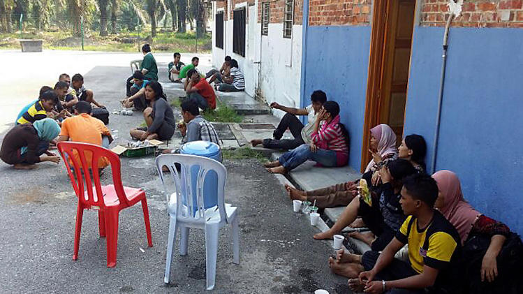 In this photo released by Malaysian Fire and Rescue Department, Indonesians rest in Carey Island, outside Kuala Lumpur, Malaysia, Wednesday, June 18, 2014, after being rescued from a boat capsized off Malaysia's west coast. At least 60 people survived when a wooden boat carrying 97 Indonesians capsized and sank early Wednesday after leaving Malaysia's west coast, but 35 others are still missing and five bodies have been recovered, Malaysia's maritime agency said. (AP Photo/Malaysian Fire and Rescue Department) EDITORIAL USE ONLY