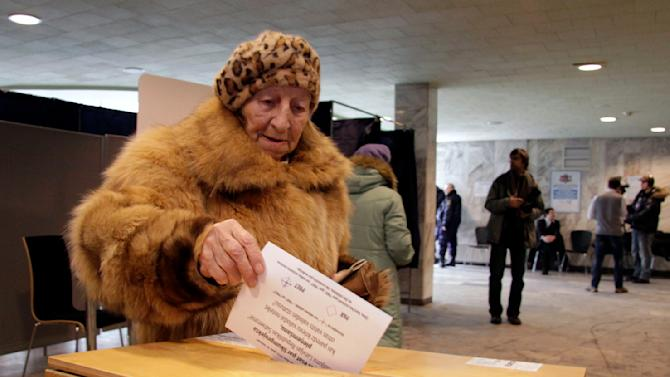 A Latvian woman casts her ballot paper at a polling station during a language referendum in Riga, Latvia, Saturday, Feb. 18, 2012. Latvia on Saturday opened a referendum on whether Russian should become the Baltic country's second national language, a poll that is likely to fail and widen the rift in an already divided society. (AP Photo/Roman Koksarov)