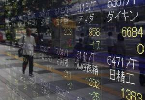 A pedestrian is reflected in an electronic board showing the various stock prices outside a brokerage in Tokyo