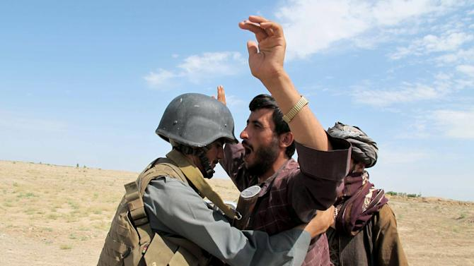 Afghan policeman inspects a passenger at a checkpoint in Helmand