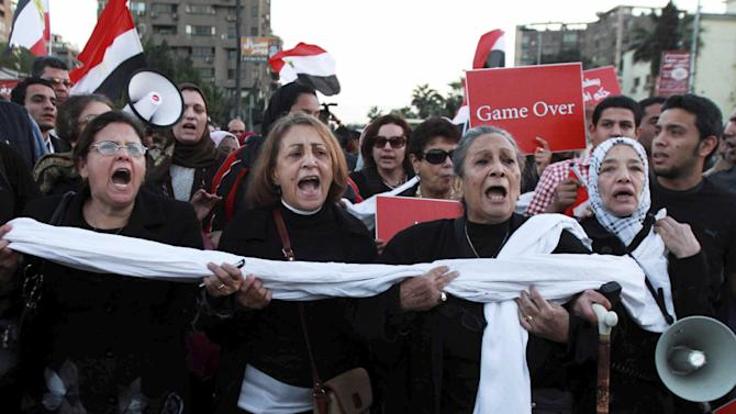 Egyptian protesters chant anti Muslim Brotherhood slogans during a demonstration near the presidential palace in Cairo, Egypt, Thursday, Dec. 6, 2012. The Egyptian army sealed off the presidential palace with barbed wire and armored vehicles Thursday as protesters defied a deadline to vacate the area, pressing forward with demands that Islamist leader Mohammed Morsi rescind decrees giving himself near-absolute power and withdraw a disputed draft constitution.(AP Photo/Ahmed Ramadan)