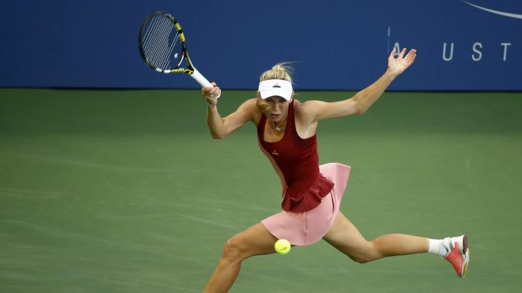 Caroline Wozniacki of Denmark hits return to Andrea Petkovic of Germany during their match at the 2014 U.S. Open tennis tournament in New York