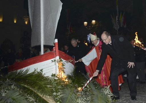 Prince Albert II of Monaco and Archbishop Bernard Barsi hold torches to burn a small fisherman's boat during the traditional Sainte Devote celebration in Monaco