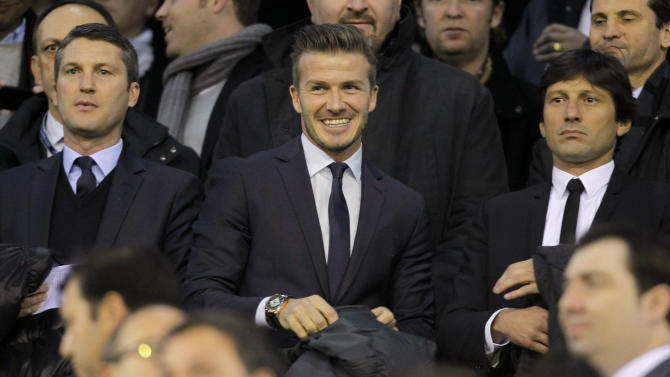 Newly signed Paris Saint-Germain player David Beckham, center, stands in the tribunes prior to a Champions League round of 16 first leg soccer match between Valencia and Paris Saint-Germain at the Mestalla stadium in Valencia, Spain, Tuesday, Feb. 12, 2013. (AP Photo/Fernando Hernandez)