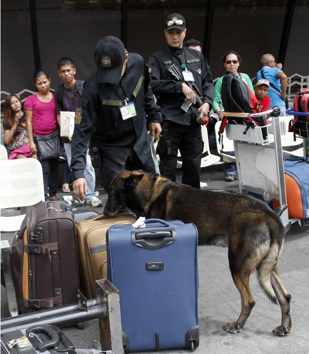A member of the Aviation Security Group of the Philippine National Police with a sniffing dog inspects baggage of a passengers atl the departure area of the International airport in Manila