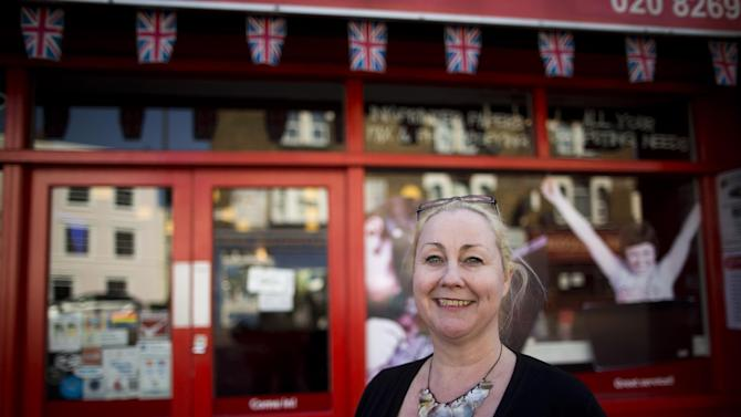 """Britain High Street Lows** Lorraine Turton, managing director of the Greenwich Communication Centre internet cafe poses for photographs outside her premises on Trafalgar Road in Greenwich, London, Tuesday, March 5, 2013.  The small shopkeepers in Greenwich are running out of time.  In the London borough that gave its name to Greenwich Mean Time, businesses like Lorraine Turton's are in danger of being relegated to history _ the victims of online shopping, changing tastes and, increasingly, the protracted recession. Her Internet cafe on Trafalgar Road is a rare hive of activity on a """"high street"""" _ the British name for a town's main business district.  (AP Photo/Matt Dunham)"""