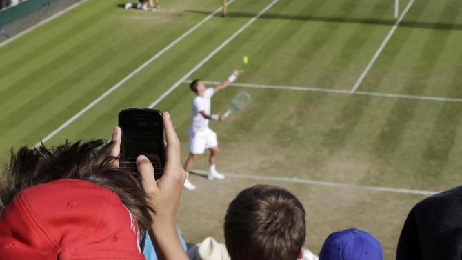 A fan takes a picture as Tomas Berdych of the Czech Republic serves during his match against Gilles Simon of France at the Wimbledon Tennis Championships in London