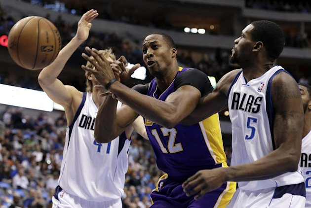 Los Angeles Lakers' Dwight Howard (12) loses control of the ball fighting for a shot attempt against Dallas Mavericks' Bernard James (5) and Dirk Nowitzki, left rear, in the first half of an NBA baske