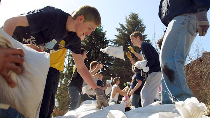 High school students toss sandbags down a line in front of homes along the Red River Friday, April 26, 2013, in Fargo, N.D. Hundreds of students pitched in, in what has become a nearly-annual sandbag party, to place 100,000 sandbags around Fargo and help protect homes against Red River flooding. (AP Photo/Dave Kolpack)