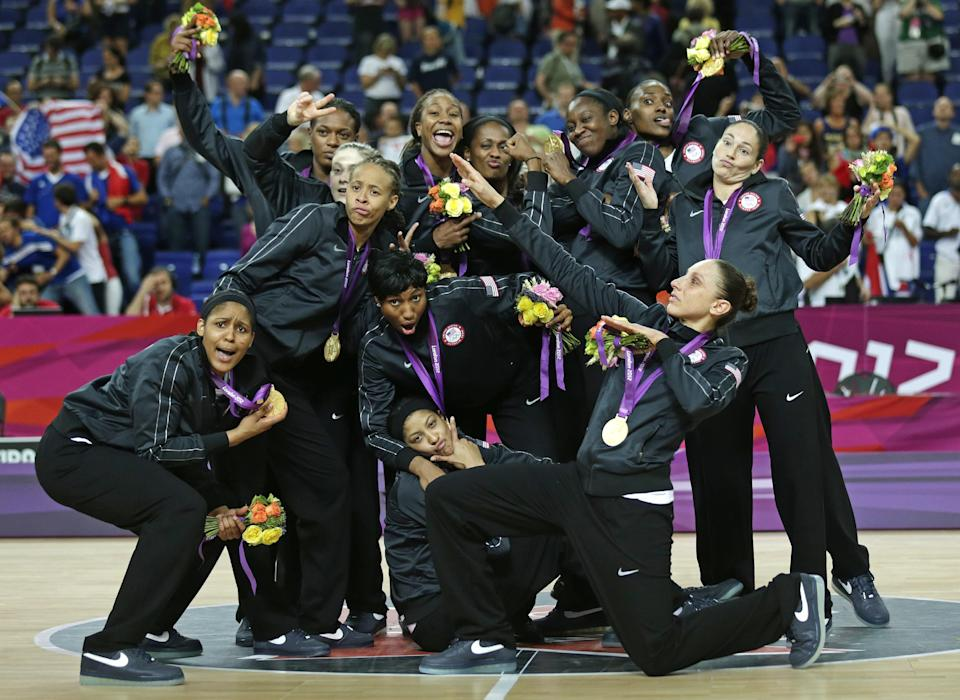 United States' poses with their gold medals at center court after beating France during the women's gold medal basketball game at the 2012 Summer Olympics, Saturday, Aug. 11, 2012, in London. (AP Photo/Charles Krupa)