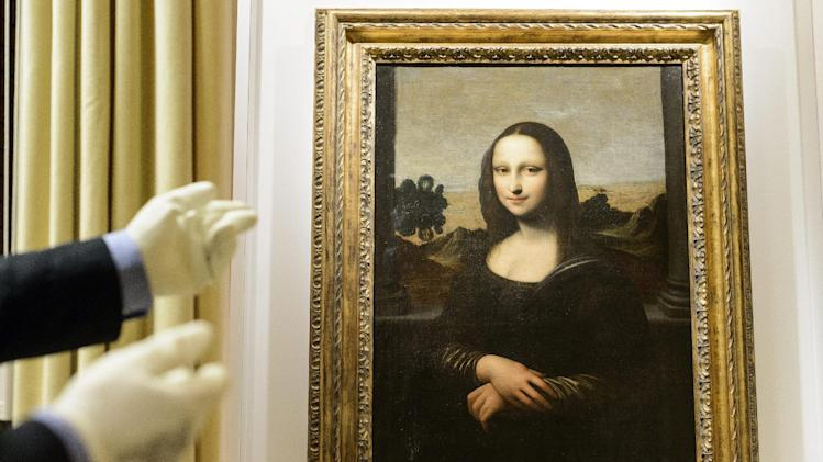 "A painting attributed to Leonardo da Vinci and representing Mona Lisa is seen during a preview presentation in a vault in Onex near Geneva, Wednesday, September 26, 2012. The Mona Lisa Foundation, a non-profit organisation based in Zurich, will present September 27, a painting and historical, comparative and scientific evidence, which demonstrate that there have always been two portraits of the Mona Lisa by Leonardo da Vinci, the ""Earlier Version"", made 10 years earlier than the ""Joconde"" that is displayed in Le Louvre in Paris. (AP Photo / KEYSTONE/Laurent Gillieron)"