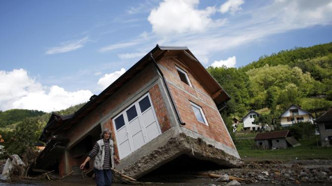 A woman reacts as she walks near a house tilted by floods in the village of Krupanj, west from Belgrade