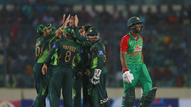 Bangladesh's Mahmudullah, right, walks back to the pavilion after his dismissal by Pakistan's Saeed Ajmal during the second one-day international cricket match in Dhaka, Bangladesh, Sunday, April 19, 2015. (AP Photo/ A.M. Ahad)