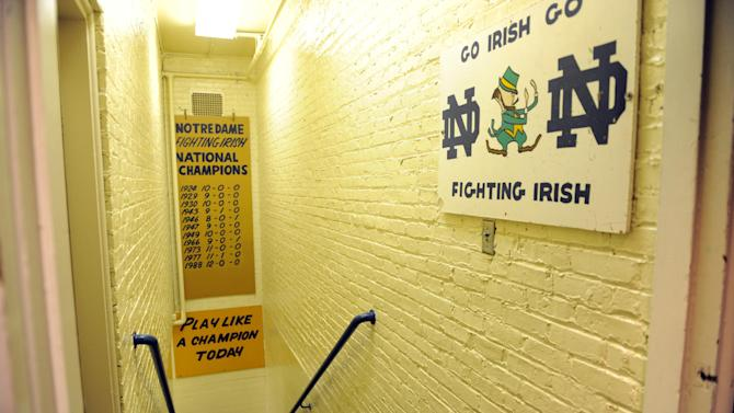 "FILE - In this Nov. 21, 2011, file photo, the hallway between the locker room and the field at Notre Dame stadium shows the sign ""Play like a Champion Today"" in South Bend, Ind. At a time when college football was generally considered the domain of eastern blue bloods, Notre Dame and Alabama were upstart teams that gave blue collar fans a chance to tweak the elite. About 90 years later, the Fighting Irish and Crimson Tide are the elite - two of college football's signature programs, set to play a national championship next Monday in Miami that could break records for television viewership. (AP Photo/Joe Raymond, File)"