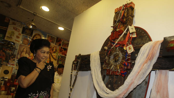"""Former Philippine first lady and now Congresswoman Imelda Marcos looks at an art installation of Catholic religious symbols by Filipino contemporary artist Mideo Cruz at Manila's Cultural Center of the Philippines, Monday, Aug. 8, 2011. The exhibit has provoked heated debate about freedom of expression in the predominantly Catholic nation. Marcos said after her visit that the work was a """"desecration"""" and no longer represents art. (AP Photo/Aaron Favila)"""