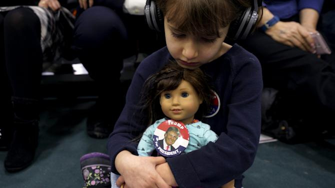 Anne-Sophie Marquis cradles her doll Clare, wearing a button supporting U.S. Republican presidential candidate Trump, at a Trump campaign rally in Plymouth