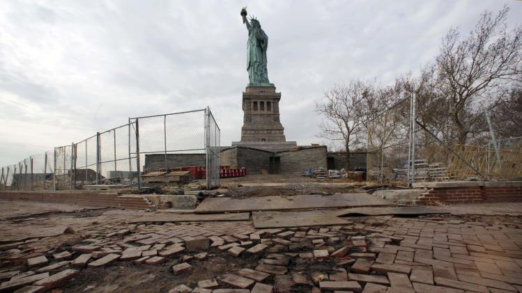 FILE - In a Nov. 30, 2012 file photo, parts of the brick walkway of Liberty Island that were damaged in Superstorm Sandy are shown during a tour of New York's Liberty Island. After hundreds of National Park Service workers from as far away as California and Alaska spent weeks cleaning and making repairs, the island will reopen to the public on Independence Day, July 4, 2013. (AP Photo/Richard Drew, File)