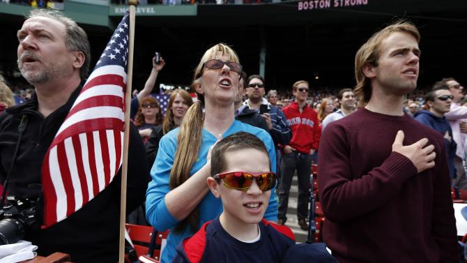 FILE - Spectators sing the national anthem before a baseball game between the Boston Red Sox and the Kansas City Royals in Boston, Saturday, April 20, 2013, five days after the bombings at the Boston Marathon. (AP Photo/Michael Dwyer)