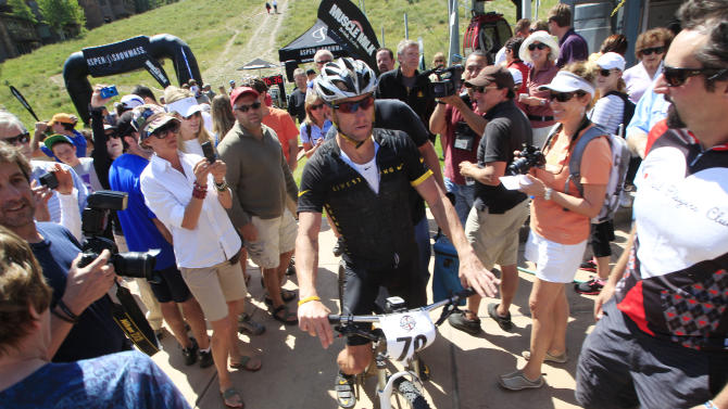 Lance Armstrong guides his bicycle through the small crowd after his second-place finish in the Power of Four mountain bicycle race at the base of Aspen Mountain in Aspen, Colo., on Saturday, Aug. 25, 2012. The race is the first public appearance for Armstrong since the U.S. Anti-Doping Association stripped him of his seven Tour de France championships and banned him for life from professional cycling. (AP Photo/David Zalubowski)