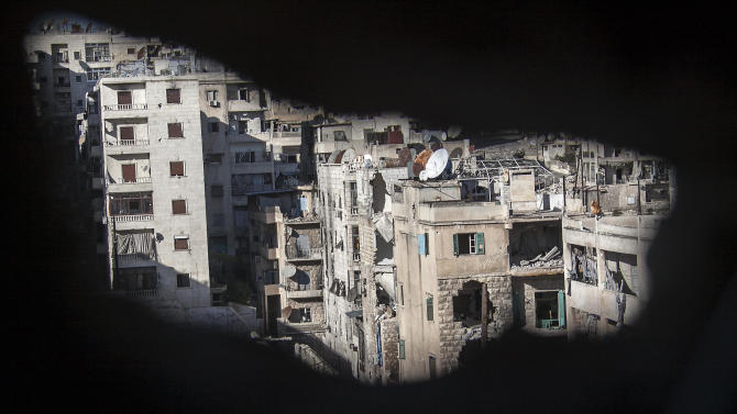 This Wednesday, Nov. 14, 2012 photo, shows destroyed buildings where Syrian army snipers are positioned, as seen through a hole in a wall in Aleppo, Syria. (AP Photo/Narciso Contreras)