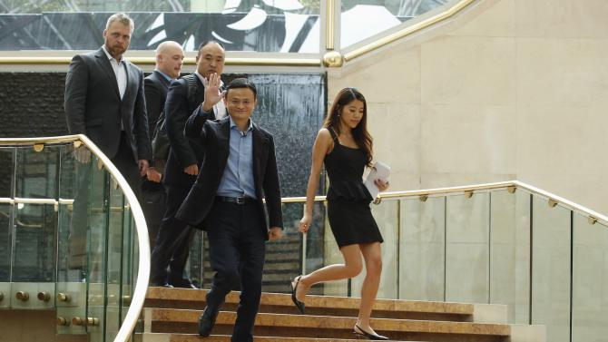 Alibaba founder Jack Ma waves as he arrives to speak to investors at an initial public offering roadshow in Singapore