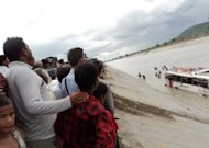 Local residents watch as a rescue team searches for the bodies of Hindu pilgrims after a bus fell into an irrigation canal near the pilgrimage site of Triveni, Nawalparasi some 100km southwest of Kathmandu, on July 15. At least 39 pilgrims were killed in the accident
