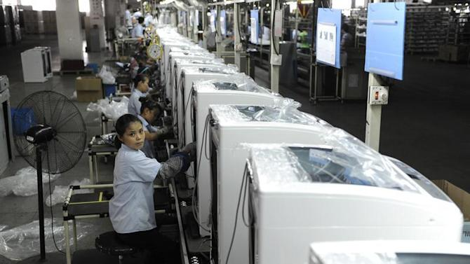 Employees assemble washing machines on the production line inside a factory of Hefei Rongshida Sanyo Electric in Hefei