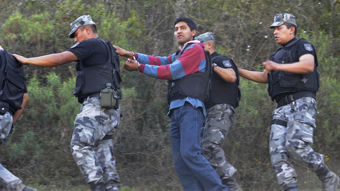 ** CORRECTS SUSPECT'S NAME IN LAST SENTENCE** Suspect Daniel Vilte, walks handcuffed and escorted by police officers in Quebrada de San Lorenzo, near Salta, Argentina, Friday Aug. 26, 2011. Vilte was taken to the area for a re-enactment of the murders of French tourists Cassandre Bouvier and Houria Moumni. Bouvier, 29, and Moumni, 23, were found on July 29 after being raped and shot to death on July 15 along a hiking and horseback riding trail in the mountainous and forested park just above the provincial capital of Salta. Vilte and two other men were arrested in connection with their rape and murders. (AP Photo/Agencia Foto Magna)