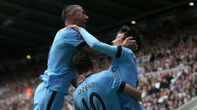 Manchester City's midfielder David Silva (R) celebrates with defender Aleksandar Kolarov (L) and striker Edin Dzeko after scoring the opening goal against Newcastle United on August 17, 2014