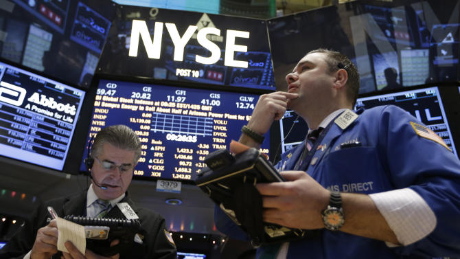 CORRECTS DATE TO 26 - Daniel Kryger, left, and Kevin Lodewick Jr., right, follow trading from the floor of the New York Stock Exchange in New York, Wednesday, Dec. 26, 2012.  (AP Photo/Kathy Willens)