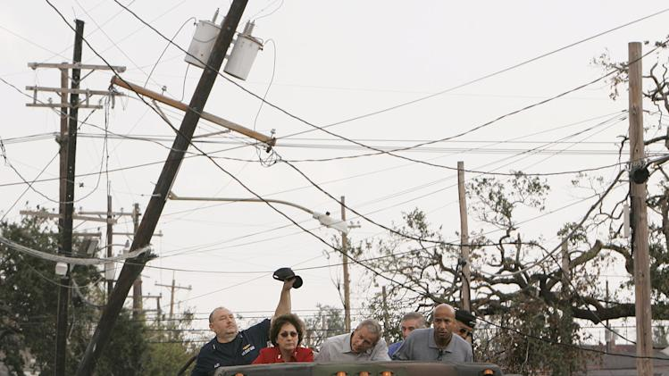 FILE - In this Monday Sept. 12, 2005 file photo, Vice Adm. Thad Allen, left, lifts a downed power line during a tour of the destruction caused by Hurricane Katrina in downtown New Orleans with President Bush, center, Lousiana Gov. Kathleen Blanco, second left, White House Chief of Staff Andrew Card, partially hidden, New Orleans Mayor Ray Nagin, second from right, and Lt. Gen. Russ Honore, right. An Associated Press analysis of outage times from other big hurricanes and tropical storms suggests that, on the whole, the utility response to Sandy, especially in hardest-hit New York and New Jersey, was typical - or even a little faster than elsewhere after other huge storms. (AP Photo/Susan Walsh, File)