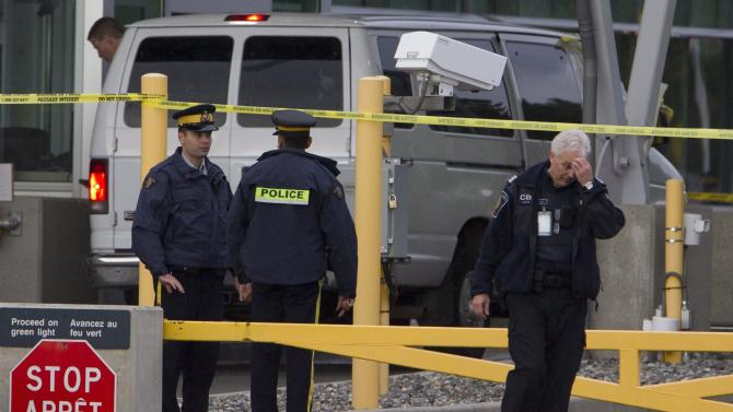 Police investigate a van at the scene of a shooting at the Blaine, Wash./Surrey, British Columbia border crossing Tuesday, Oct. 16, 2012. Royal Canadian Mounted Police Cpl. Bert Paquet says a border officer was in her booth when she was shot in the neck at about 2 p.m. Tuesday by a man trying to enter Canada in a van with Washington state plates. (AP Photo/The Canadian Press, Jonathan Hayward)
