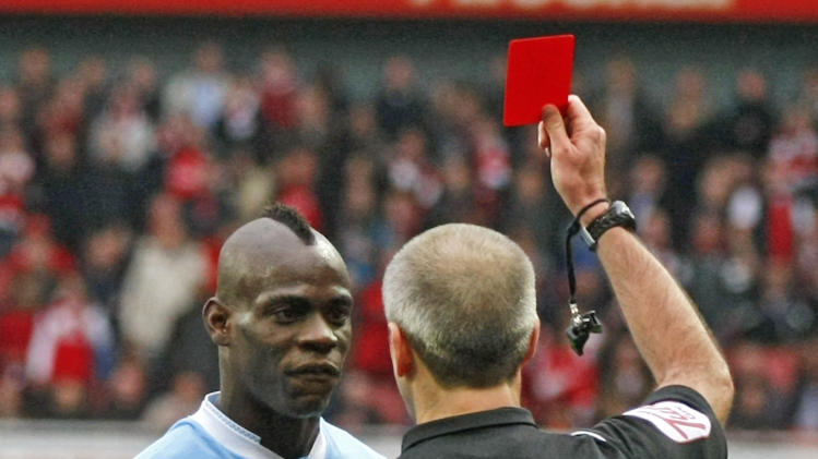 FILE - In this Sunday, April 8, 2012 file photo Manchester City's Mario Balotelli, left, is shown a red card by referee Martin Atkinson during their English Premier League soccer match against Arsenal at the Emirates stadium, London. AC Milan says it has reached agreement with Manchester City to sign Mario Balotelli. (AP Photo/Tim Hales, File)