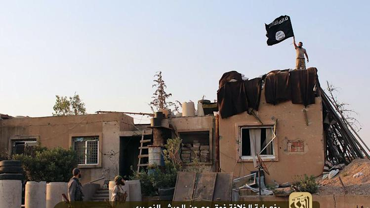 An image made available by Jihadist media outlet Welayat Raqa on July 25, 2014, shows allegedly shows members of the Islamic state militant group raising their black and white flag over a building belonging to the Syrian army in Raqa