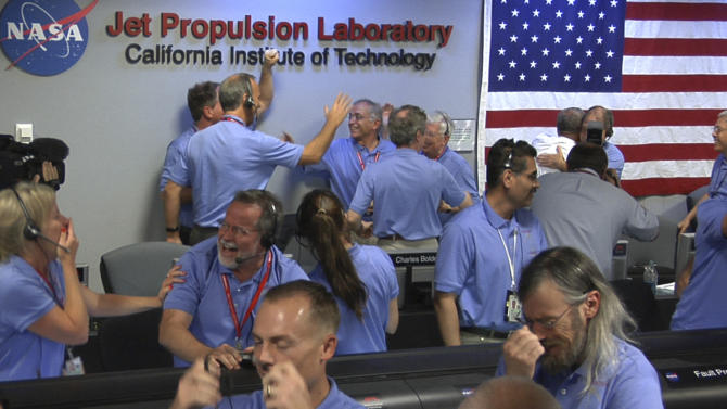 In this photo released by NASA/JPL-Caltech, Mars Science Laboratory (MSL) team members react after the Curiosity rover successfully landed on Mars and as first images start coming in to the Jet Propulsion Laboratory, Sunday, Aug. 5, 2012 in Pasadena, Calif.(AP Photo/NASA/JPL-Caltech)