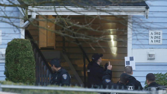 Investigators examine the stairwell of an apartment complex, Monday, April 22, 2013, in Federal Way, Wash., where an overnight shooting left five people dead., including a suspect who was shot by arriving officers, police said early Monday. (AP Photo/Ted S. Warren)