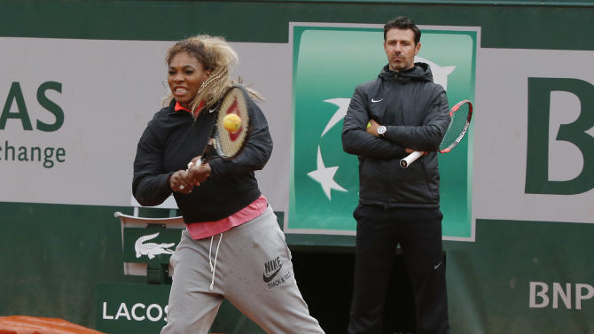 Serena Williams of the U.S., returns the ball while her coach Patrick Mouratoglou, right, looks on during a training session for the French Open tennis tournament, at the Roland Garros stadium in Paris, Saturday, May 24, 2014. The French Open tennis tournament starts Sunday. (AP Photo/Michel Euler)