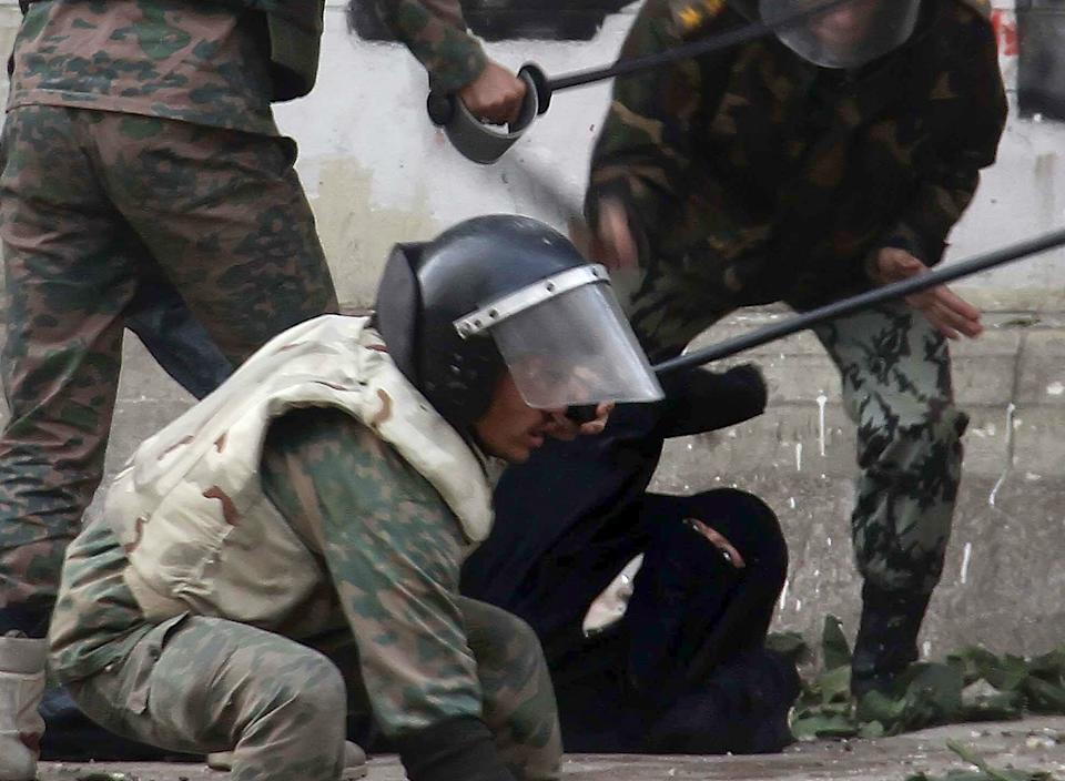 Egyptian army soldiers rear arrest a woman protester wearing the Niqab during clashes near Cairo's downtown Tahrir Square, Egypt, Friday, Dec. 16, 2011. Activists say the clashes began after soldiers severely beat a young man who was part of a sit-in outside the Cabinet building.  (AP Photo/Ahmed Ali)