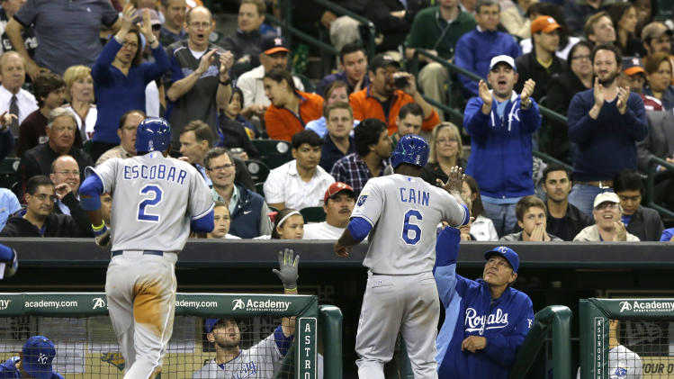 Kansas City Royals Alcides Escobar (2) and Lorenzo Cain (6) are welcomed back to the dugout after scoring on a bases-loaded single against the Houston Astros by Salvador Perez in the seventh inning of a baseball game Wednesday, April 16, 2014, in Houston. (AP Photo/Pat Sullivan)
