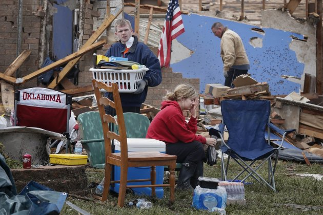 Resident Taylor Tennyson sits in the front yard as family members salvage the remains from their home which was left devastated by a tornado in Moore, Oklahoma