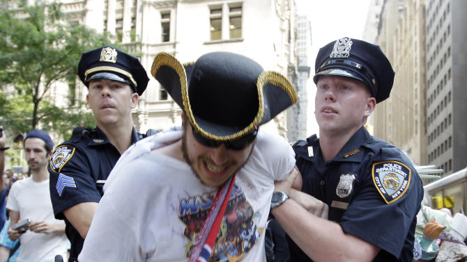 An Occupy Wall Street protestor is arrested in Zuccotti Park Wednesday, July 11, 2012, in New York.  Occupy marchers with guitars are marking the 100th birthday of the late folk singer-songwriter Woody Guthrie with a Manhattan rally. It's called Occupy Guitarmy.  They ended a six-day march from the Liberty Bell in Philadelphia on Wednesday afternoon in Zuccotti Park. The lower Manhattan park was the center of the Occupy movement until police broke up the encampment last November.  (AP Photo/Frank Franklin II)